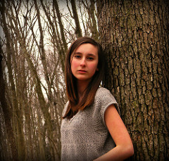 sad girl leaning against tree