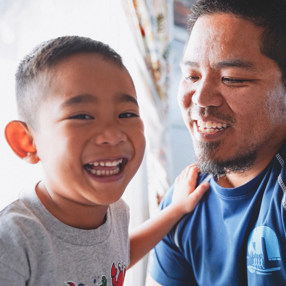 Young boy laughing with father.
