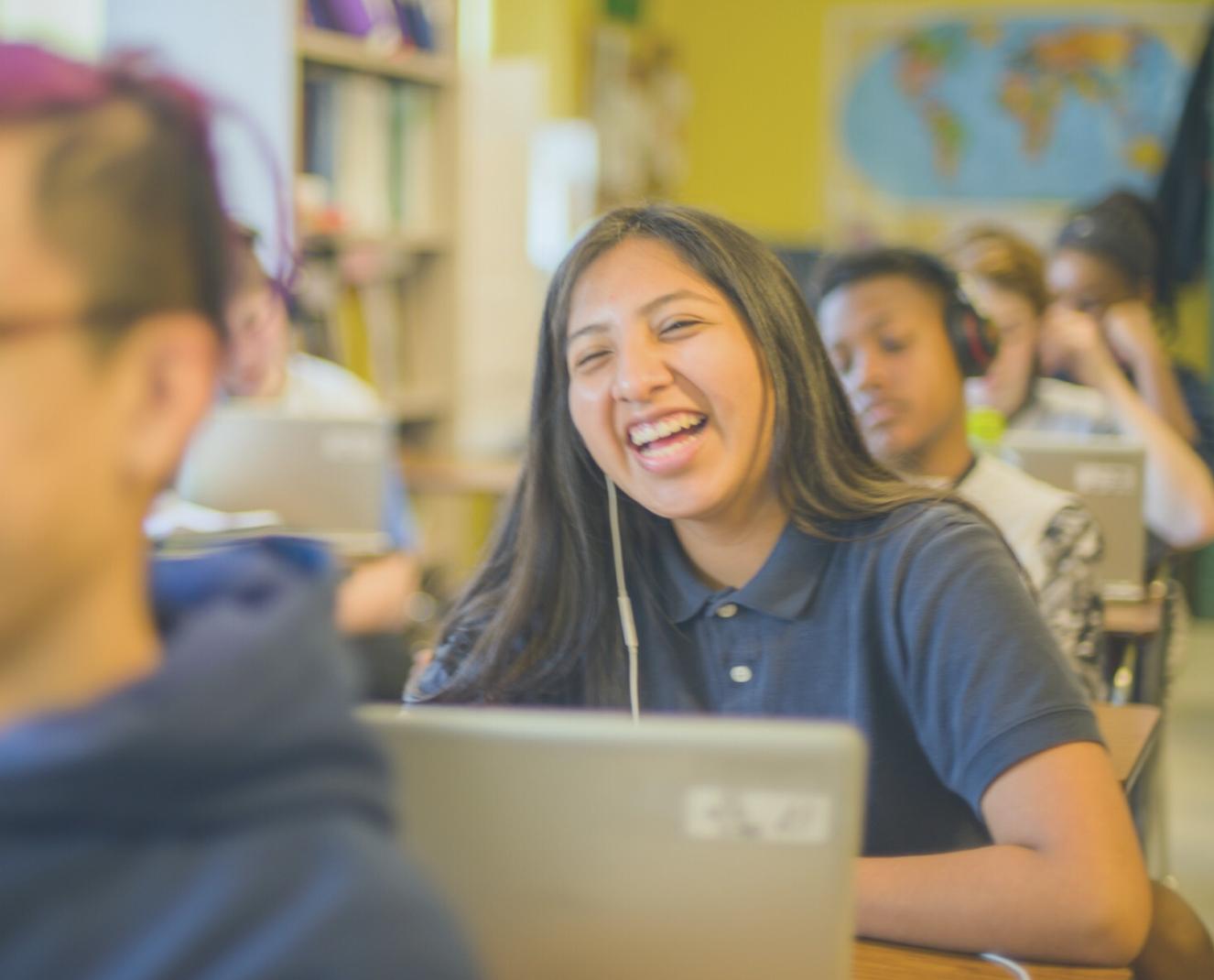 Teen girl laughing in class