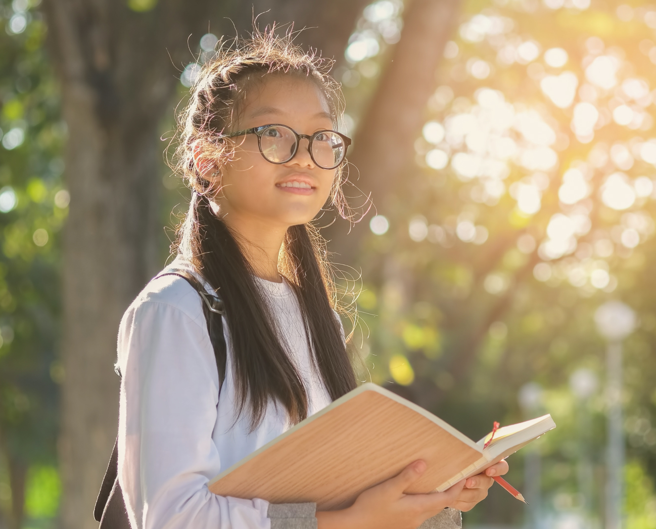 Young girl smiling outdoors with a schoolbook