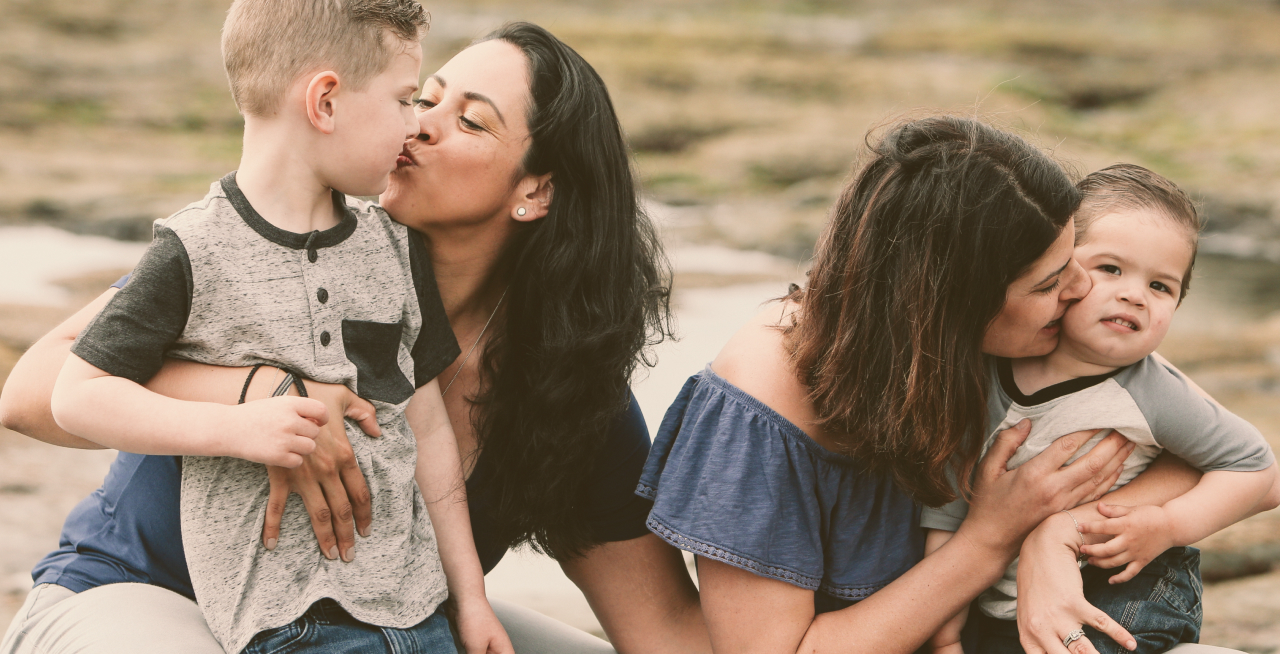 Two women kissing their toddlers