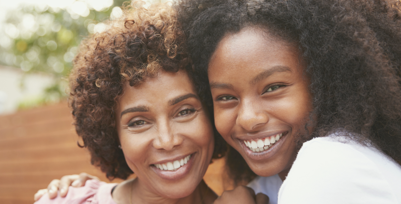 Woman and her teen daughter smiling